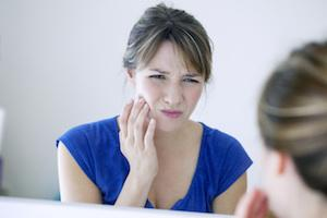 woman looking in mirror with tooth pain
