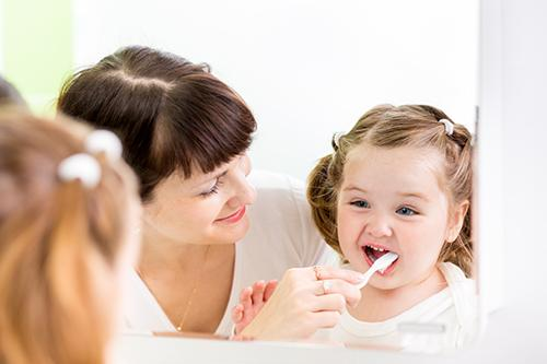 baby with mum brushing teeth